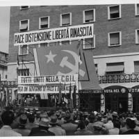 Anni Cinquanta, manifestazione elettorale del PCI, in Piazza Matteotti, Modena. I manifesti coprono la facciata della libreria Rinascita, il cui ingresso era sotto al portico [ISMO, APCMO]
