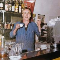 """1966. Borgo San Giuliano. Il Socio """"Purchera"""", con sigaretta e caffè, dietro al bancone del Circolo"""