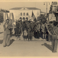 24 aprile 1945, partigiani sfilano in piazza della Vittoria verso quella che diventerà piazza Martiri del 7 luglio 1960 in occasione della Liberazione di Reggio Emilia