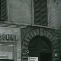 """Novembre 1956. Rimini, Corso d'Augusto. L'ingresso alla sede della Federazione. Sul portone il manifesto """"Provocatori e incendiari"""" dopo l'assalto dei missini a seguito dell'invasione russa dell'Ungheria"""