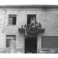 Gruppo di giovani donne affacciate a un balcone, con la bandiera della federazione modenese della FGCI [ISMO, AFPCMO]
